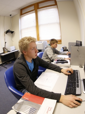 one student uses a computer to engage with distance learning classmates