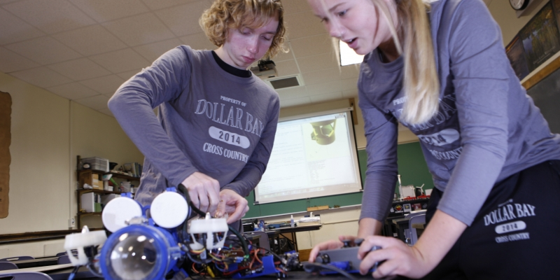 two high school students work on a marine robot